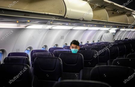 A passengers sits in a mostly empty airplane wearing protection mask against the coronavirus during the flight bound from Sihanoukville, Cambodia via Phnom Penh, Cambodia to Guangzhou, Guangdong Province, China, 01 February 2020. Guangzhou Airport, usually busy during the end of Spring Festival when Chinese travelers return to their homes, appeared deserted after many countries and international airlines suspended or limited flights to and from China, because of outbreak of coronavirus in Wuhan City.