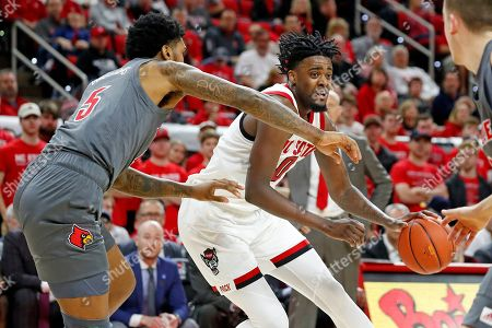 North Carolina State's DJ Funderburk (0) drives the ball as Louisville's Malik Williams (5) defends during the first half of an NCAA college basketball game in Raleigh, N.C