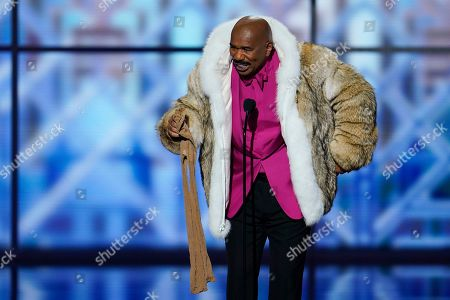 Comedian Steve Harvey wears a fur coat once owned by former NFL player Joe Namath at the NFL Honors football award show, in Miami