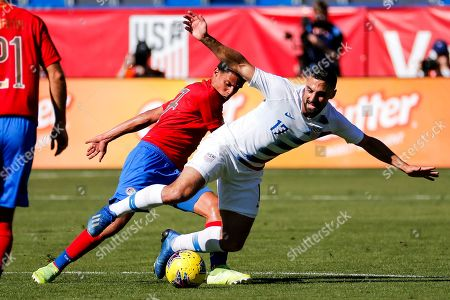 Stock Picture of United States midfielder Sebastian Lletget (17) is tackled from behind by Costa Rica midfielder Yeltsin Tejeda (17) during the first half of an international friendly soccer match in Carson, Calif