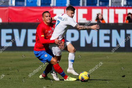 Costa Rica midfielder David Guzman (20) grabs United States forward Paul Arriola (7) during the first half of an international friendly soccer match in Carson, Calif
