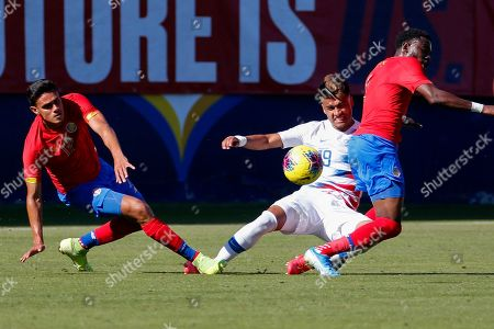 United States forward Ulysses Llanez, center, slides between Costa Rica midfielder Yeltsin Tejeda, left, and defender Keysher Fuller (4) during the first half of an international friendly soccer match in Carson, Calif