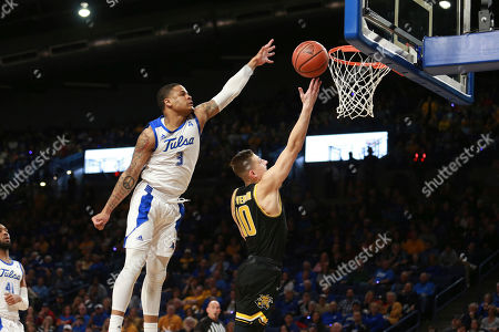 Stock Image of Tulsa guard Elijah Joiner (3) blocks the shot of Wichita State guard Erik Stevenson (10) in the first half of an NCAA college basketball game in Tulsa, Okla