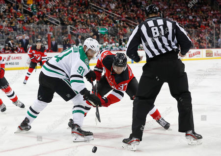 Dallas Stars center Tyler Seguin (91) and New Jersey Devils center Pavel Zacha (37) battle for the puck during the second period of an NHL hockey game, in Newark, N.J