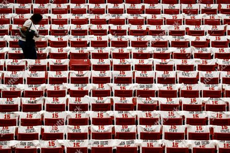 A fan heads to her seat among replica jerseys in honor of former San Diego State basketball player Kawhi Leonard before San Diego State's NCAA college basketball game against Utah State, in San Diego