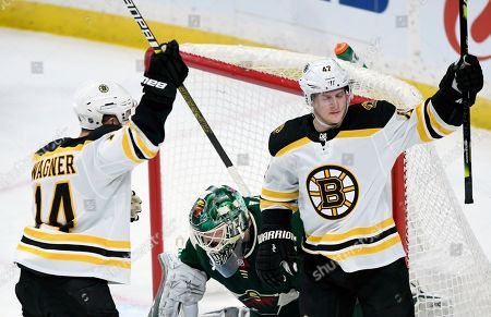 Boston Bruins' Chris Wagner (14) and Torey Krug (47) celebrate a goal by Krug as Minnesota Wild goaltender Devan Dubnyk (40) watches during the first period of an NHL hockey game, in St. Paul, Minn