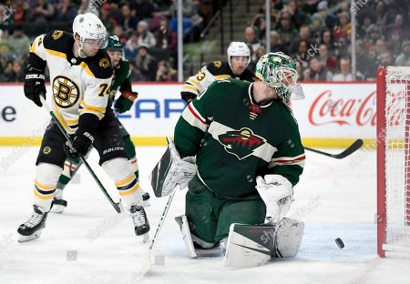Minnesota Wild goaltender Devan Dubnyk (40) and Boston Bruins left wing Jake DeBrusk (74) watch as the shot by Boston Bruins' Torey Krug, not pictured, goes into the net during the second period of an NHL hockey game, in St. Paul, Minn