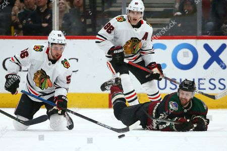 Chicago Blackhawks defenseman Erik Gustafsson (56) passes the puck after colliding with Arizona Coyotes center Derek Stepan, right, as Blackhawks right wing Patrick Kane (88) watches during overtime of an NHL hockey game, in Glendale, Ariz. The Blackhawks won 3-2 in a shootout