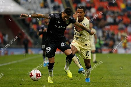 Juarez's Bruno Romo, front, defends challenged by America's Giovani Dos Santos during a Mexican soccer league match at Azteca stadium in Mexico City