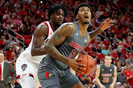 Stock Picture of Malik Williams, DJ Funderburk. Louisville's Malik Williams (5) tries to shoot over North Carolina State's DJ Funderburk (0) during the second half of an NCAA college basketball game in Raleigh, N.C