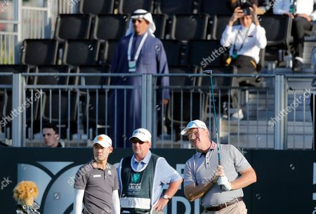 South Africa's Ernie Els, right, follows his ball on the first hole during the final round of the Saudi International at Royal Greens Golf and Country Club, in Red Sea resort of King Abdullah Economic City, Saudi Arabia