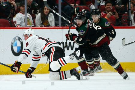 Arizona Coyotes right wing Clayton Keller (9) trips Chicago Blackhawks center Jonathan Toews, left, for a penalty as Coyotes center Nick Schmaltz (8) looks on during the first period of an NHL hockey game, in Glendale, Ariz. The Blackhawks defeated the Coyotes 3-2 in a shootout