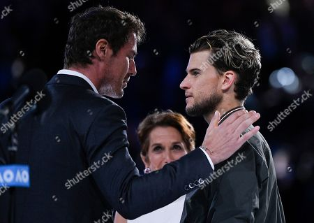 Austria's Dominic Thiem is consoled by former champion Marat Safin after finishing runner-up to Serbia's Novak Djokovic in the men's singles final at the Australian Open tennis championship in Melbourne, Australia