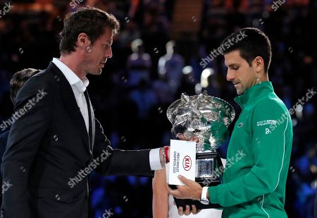 Serbia's Novak Djokovic, right, receives the Norman Brooks Challenge Cup from former champion Marat Safin after defeating Austria's Dominic Thiem in the men's singles final of the Australian Open tennis championship in Melbourne, Australia, early
