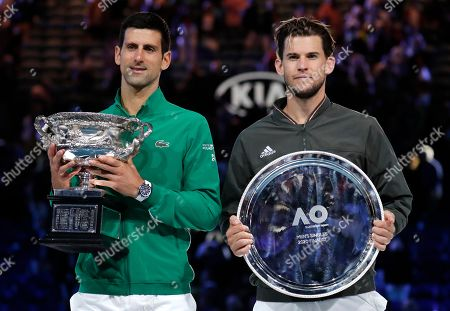 Serbia's Novak Djokovic, left, holds the Norman Brooks Challenge Cup after defeating Austria's Dominic Thiem in the men's singles final of the Australian Open tennis championship in Melbourne, Australia, early