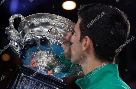 Serbia's Novak Djokovic kisses the Norman Brookes Challenge Cup after defeating Austria's Dominic Thiem in the final of the Australian Open tennis championship in Melbourne, Australia