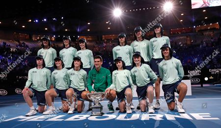 Serbia's Novak Djokovic poses for a photo the Norman Brookes Challenge Cup with the ballkids after defeating Austria's Dominic Thiem in the men's singles final of the Australian Open tennis championship in Melbourne, Australia, early