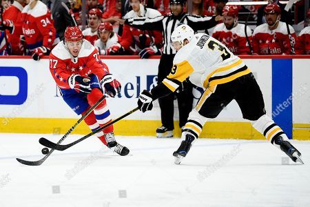 Washington Capitals right wing T.J. Oshie (77) and Pittsburgh Penguins defenseman Jack Johnson (3) battle for the puck during the second period of an NHL hockey game, in Washington