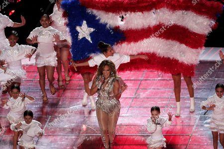 Jennifer Lopez and daughter Emme Maribel Muniz, behind, perform during halftime of the NFL Super Bowl 54 football game, in Miami Gardens, Fla