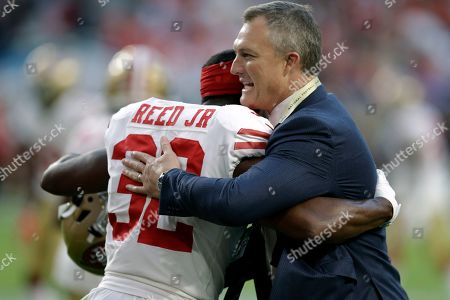 San Francisco 49ers general manager John Lynch, right, embraces D.J. Reed Jr., on the field before the NFL Super Bowl 54 football game against the Kansas City Chiefs, in Miami Gardens, Fla