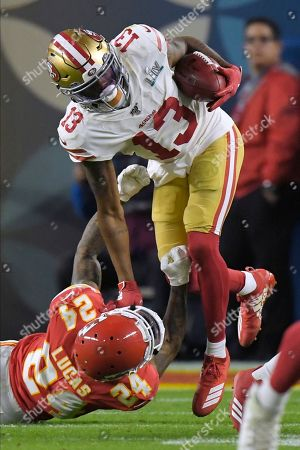Stock Photo of Kansas City Chiefs Jordan Lucas, left, tackles San Francisco 49ers Richie James during the second half of the NFL Super Bowl 54 football game, in Miami Gardens, Fla