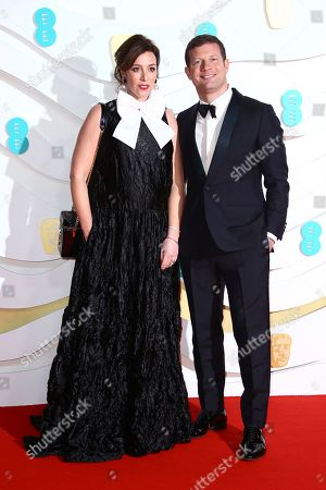 Dermot O'Leary, Dee Koppang. Dermot O'Leary, right and Dee Koppang pose for photographers upon arrival at the Bafta Film Awards, in central London