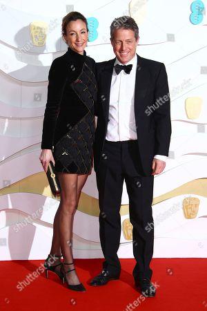 Anna Elisabet Eberstein, Hugh Grant. Actor Hugh Grant, right and Anna Elisabet Eberstein pose for photographers upon arrival at the Bafta Film Awards, in central London