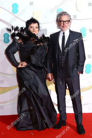 Stock Image of Dalia Ibelhauptaite, Dexter Fletcher. Dexter Fletcher, right and Dalia Ibelhauptaite pose for photographers upon arrival at the Bafta Film Awards, in central London