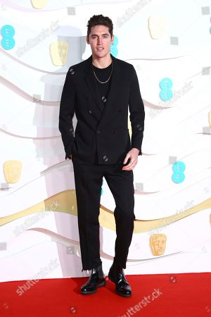 Isaac Carew poses for photographers upon arrival at the Bafta Film Awards, in central London