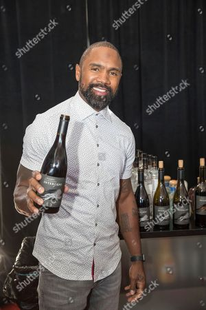 Hall of Fame NFL player Charles Woodson poses with a bottle of his new wine, Intercept, at the Players Tailgate at Super Bowl LIV, in Miami