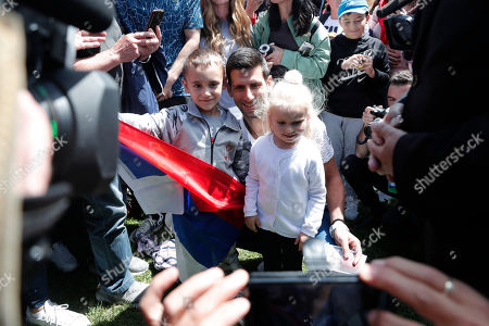 Serbia's Novak Djokovic poses with children during a photo shoot at Melbourne's Royal Botanic Gardens following his win over Austria's Dominic Thiem in the men's singles final of the Australian Open tennis championship in Melbourne, Australia