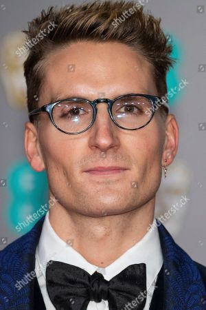 Oliver Proudlock poses for photographers upon arrival at the Bafta Film Awards, in central London