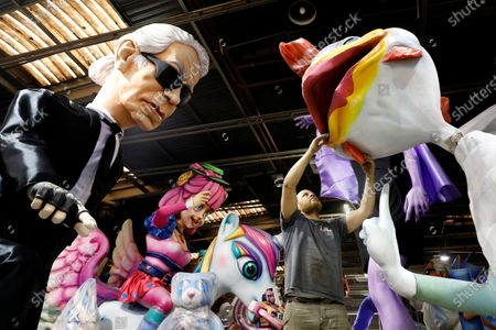 A man works next to a carnival character depicting the late German designer Karl Lagerfeld (L) during preparations for the 2020 Nice Carnival, in Nice, France, 03 February 2020. The annual Carnival of Nice will run from 15 to 29 February 2020, and the main theme will be 'King of Fashion'