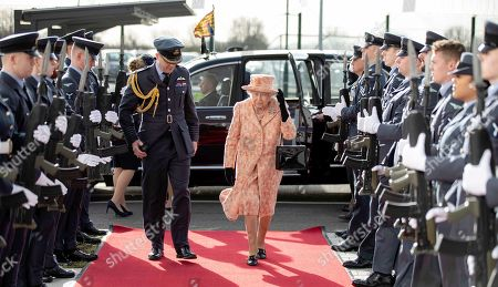 Queen Elizabeth II is escorted past an RAF guard of honour as she arrives at RAF Marham to inspect the new integrated training centre that trains personnel on the maintenance of the new RAF F-35B Lightning II strike aircraft. With her is Station commander Group captain James Beck.
