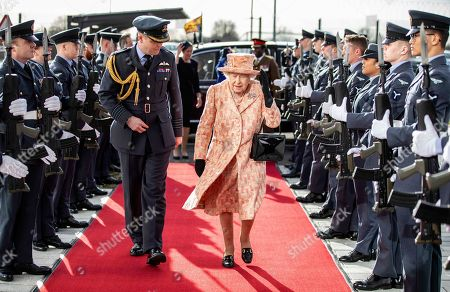 Stock Image of Queen Elizabeth II is escorted past an RAF guard of honour as she arrives at RAF Marham to inspect the new integrated training centre that trains personnel on the maintenance of the new RAF F-35B Lightning II strike aircraft. With her is Station commander Group captain James Beck.