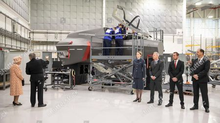 Queen Elizabeth II is greeted by Personnel at RAF Marham where she inspected the new integrated training centre that trains personnel on the maintenance of the new RAF F-35B Lightning II strike aircraft. With her is Station commander Group captain James Beck.