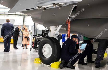 Queen Elizabeth II watches air crew at work on a training model F-35B Lightning II fighter at RAF Marham where she inspected the new integrated training centre that trains personnel on the maintenance of the new RAF F-35B Lightning II strike aircraft. With her is Station commander Group captain James Beck.