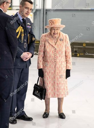 Stock Photo of Queen Elizabeth II watches air crew at work on a training model F-35B Lightning II fighter at RAF Marham where she inspected the new integrated training centre that trains personnel on the maintenance of the new RAF F-35B Lightning II strike aircraft. With her is Station commander Group captain James Beck.