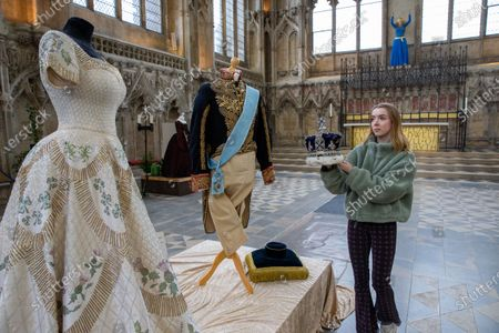 Stock Picture of Rhiannon Ankers, a volunteer at Ely cathedral, with the crown used in 'The Crown' alongside a costume that was used on the show and worn by Claire Foy, which is on display during the exhibition.
