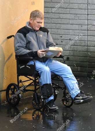 Stock Image of Ronnie Ramsay sits in a wheelchair smoking a cigarette