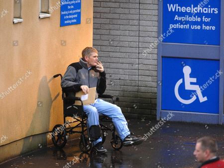 Ronnie Ramsay sits in a wheelchair smoking a cigarette
