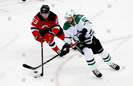 Dallas Stars center Tyler Seguin (91) and New Jersey Devils left wing Jesper Bratt (63) plays the puck against during the third period of an NHL hockey game, in Newark,N.J