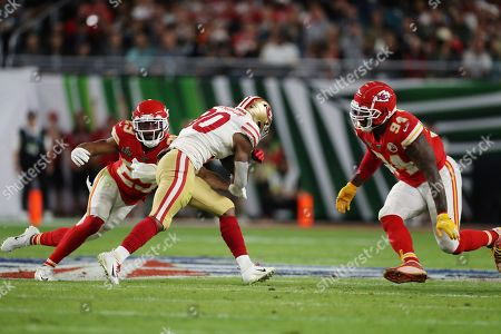 Kansas City Chiefs cornerback Kendall Fuller (29) and Kansas City Chiefs outside linebacker Terrell Suggs (94) tackle San Francisco 49ers running back Jeff Wilson (30) during the first half of the NFL Super Bowl 54 football game between the San Francisco 49ers and Kansas City Chiefs, in Miami Gardens, Fla. The Kansas City Chiefs won 31-20