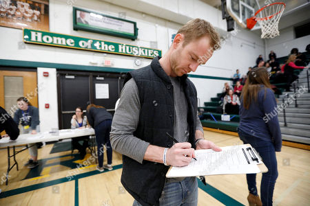 Stephen Smith of Des Moines, Iowa, fills out a change of party form before an Iowa Democratic caucus at Hoover High School, in Des Moines, Iowa