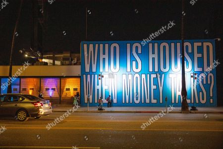 """Stock Picture of IMAGE DISTRIBUTED FOR AIDS HEALTHCARE FOUNDATION - Legendary artist Barbara Kruger's latest word-text mural, """"WHO IS HOUSED WHEN MONEY TALKS?"""", is seen on the Sunset Boulevard headquarters of the Rental Affordability Act during a party and press conference celebrating the certification of voter signatures in support of the proposed statewide initiative that will allow for expansion of rent control throughout California. Earlier in the day, Secretary of State Alex Padilla's office announced they had certified enough signatures to advance the measure for placement on the November 2020 statewide ballot. Kruger donated the mural pro bono to the group Housing Is A Human Right, an advocacy arm of AIDS Healthcare Foundation, which submitted over 1 million voter signatures in early December to qualify the ballot measure and the party and press conference, one of three statewide, on in Los Angeles"""