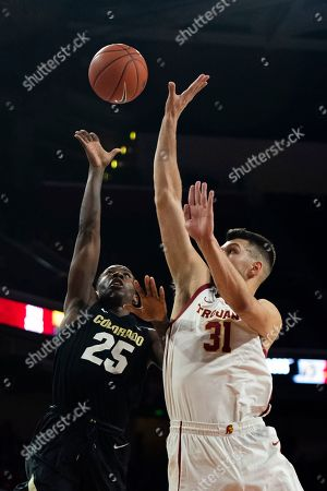 Colorado guard McKinley Wright IV, left, shoots over Southern California forward Nick Rakocevic in an NCAA college basketball game in Los Angeles