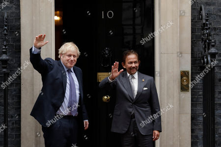 British Prime Minister Boris Johnson waves at the media as he greets the Sultan of Brunei, Hassanal Bolkiah before their meeting at 10 Downing Street in London