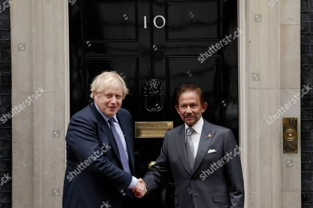 British Prime Minister Boris Johnson, left, shakes hands for the media as he greets the Sultan of Brunei, Hassanal Bolkiah before their meeting at 10 Downing Street in London