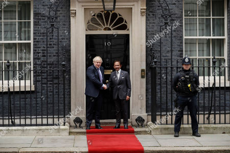 British Prime Minister Boris Johnson shakes hands for the media as he greets the Sultan of Brunei, Hassanal Bolkiah before their meeting at 10 Downing Street in London