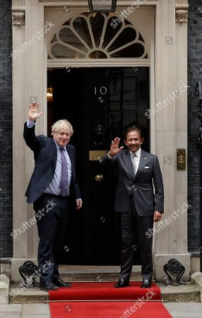 British Prime Minister Boris Johnson, left, waves at the media as he greets the Sultan of Brunei, Hassanal Bolkiah before their meeting at 10 Downing Street in London